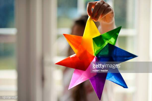 child holding a rainbow of hope star for covid-19 - star shape stock pictures, royalty-free photos & images