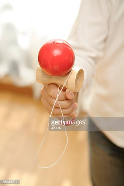 A child holding a traditional kendama toy