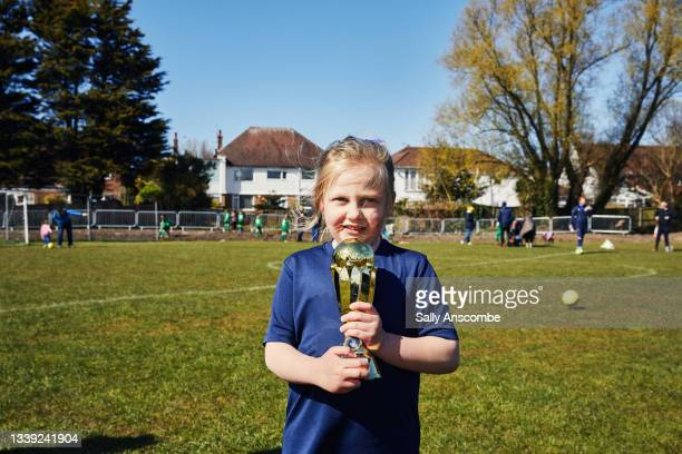 child holding a trophy after a football match - club football stock pictures, royalty-free photos & images