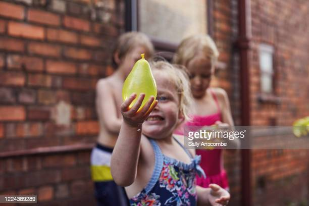 child holding a water balloon - messing about stock pictures, royalty-free photos & images