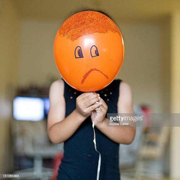 Child holding an orange balloon with sad face