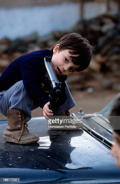 A child holding and pointing a weapon Italian US and French troops recently left the Lebanese territory after the international intervention due to...
