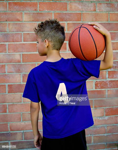 child holding basketball near brick wall