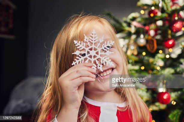 child holding christmas decorations - sally anscombe stock pictures, royalty-free photos & images
