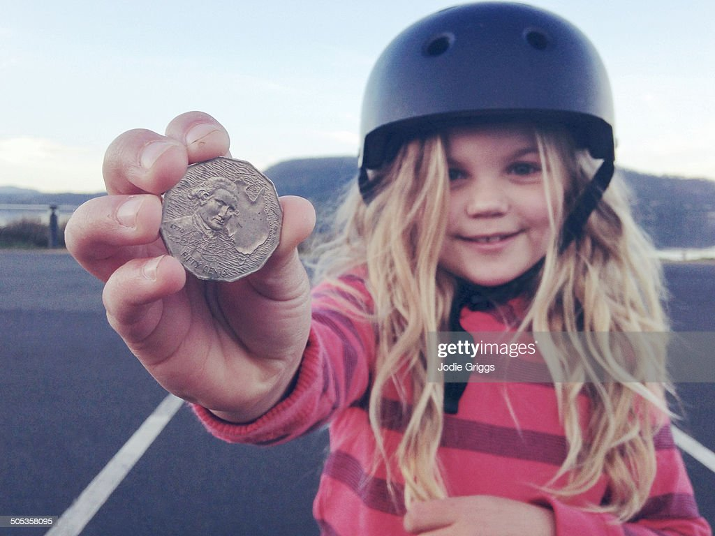 Child holding coin that she found on the ground : Stock Photo