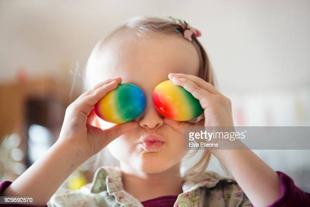 Child holding colorful painted eggs over eyes