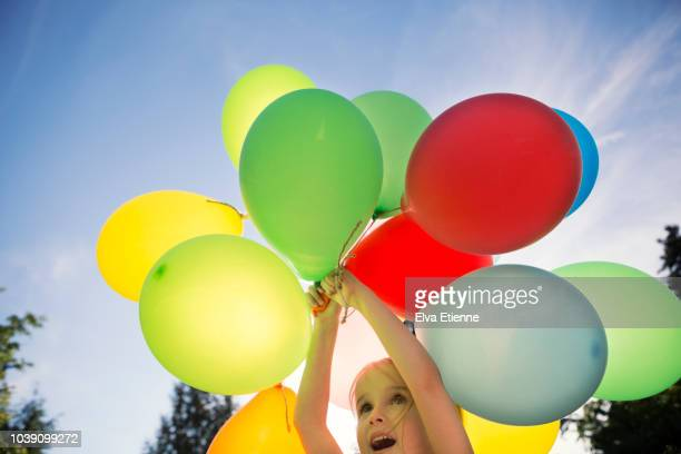 child holding colourful balloons up against a clear blue sky - latex stock pictures, royalty-free photos & images