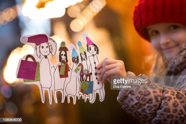 child (6-7) holding drawing of a happy family, christmas shopping together at a german christmas market - レオパード柄 ストックフォトと画像