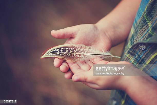 Child holding feather