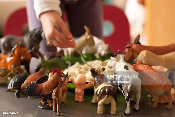 Child holding fork and animals around