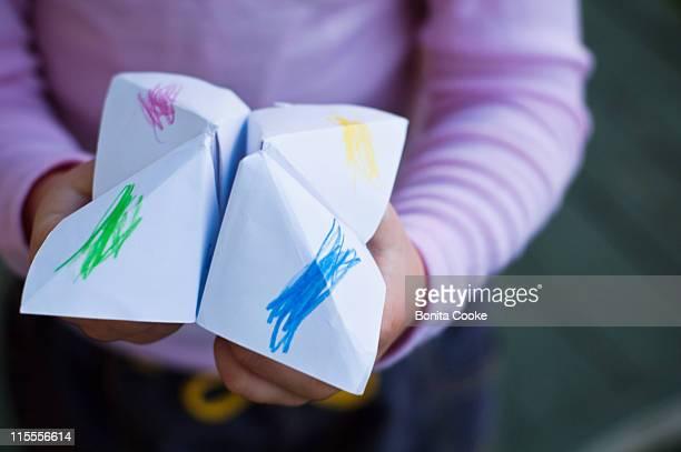 Child holding fortune teller paper game