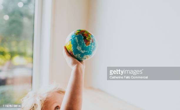 child holding globe ball - globe stock pictures, royalty-free photos & images