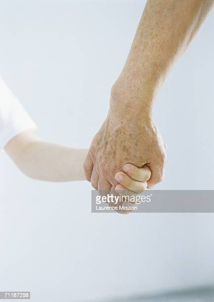 child holding grandparent's hand - lentigo stock pictures, royalty-free photos & images
