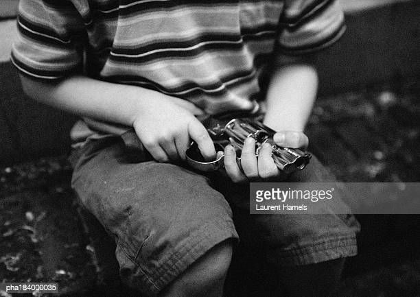 Child holding gun, mid-section, b&w