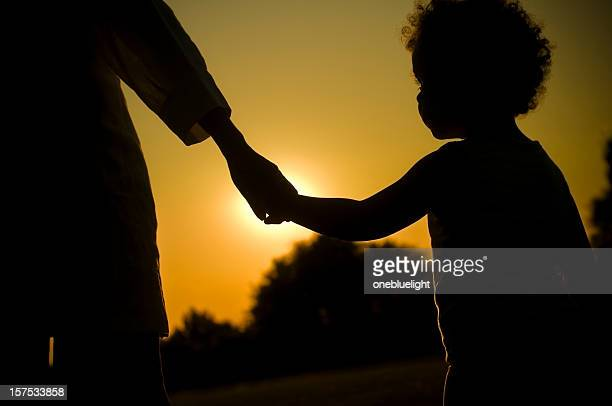 Child Holding Hands of her Mother at Sunset