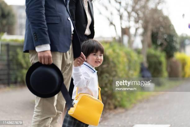 親の手で手をつないでいる子供 - よそいきの服 ストックフォトと画像