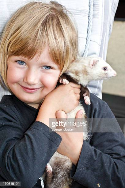 Child holding her pet ferret as her friend