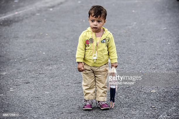 A child holding his doll stands on a road close to a makeshift camp setup by refugees and migrants on the Serbian side of at the Hungarian border...