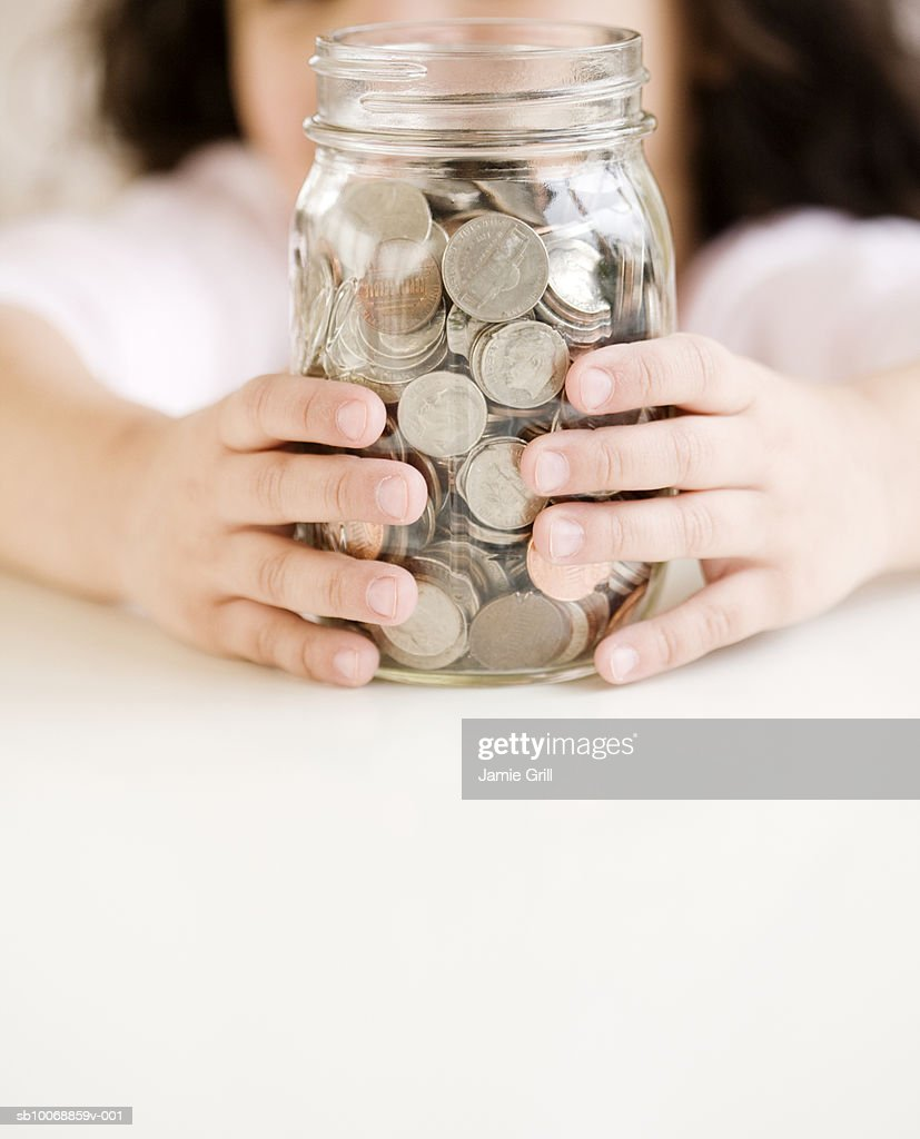 Child holding jar of coins, close-up, mid section : Stock Photo