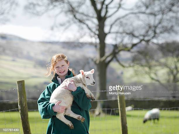 Child holding lamb smiling