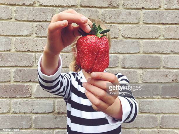 Child holding large strawberry in front of face