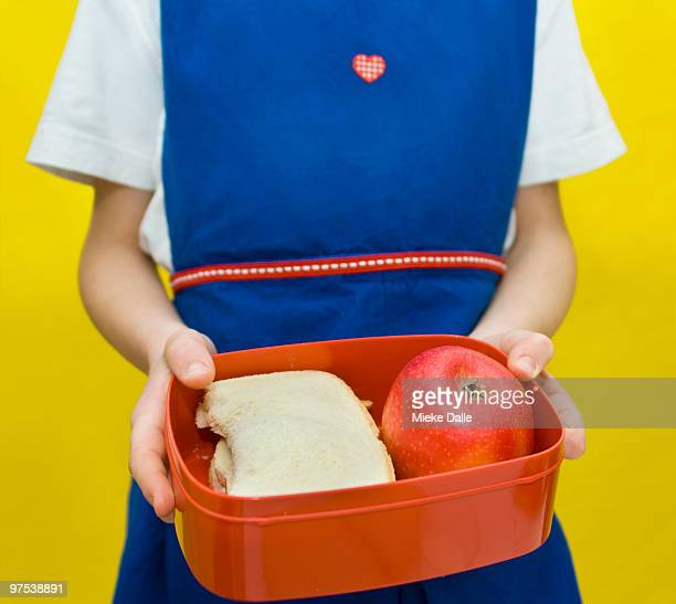 child holding lunch box with healthy food
