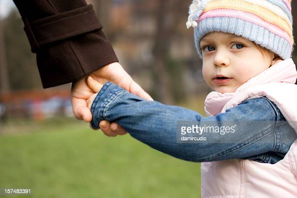 child holding mother's hand - adoptie stockfoto's en -beelden