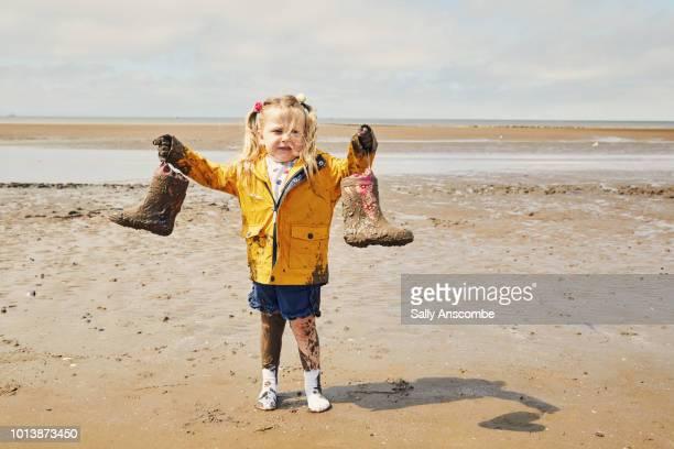 Child holding muddy wellington boots