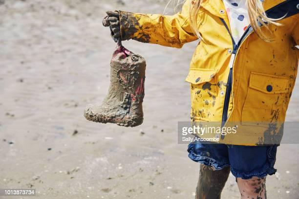 child holding muddy wellington boots - schlamm stock-fotos und bilder