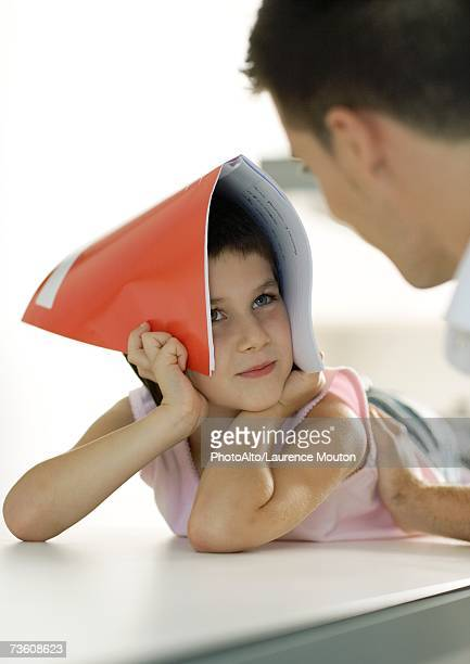 Child holding notebook over head, looking at father