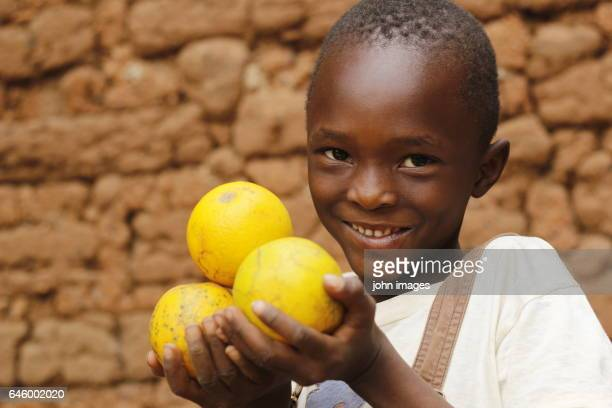 A child holding oranges