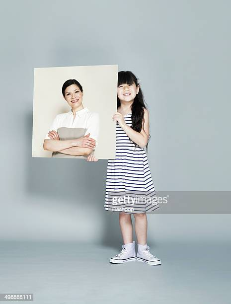 child holding picture of inspirational person - nice girls pic stock photos and pictures