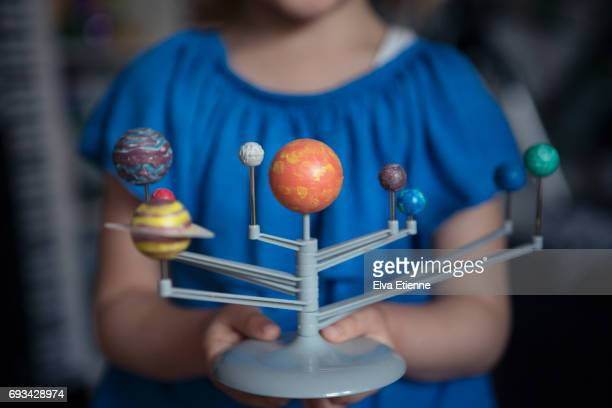 child holding plastic model of the planets in our solar system - sistema solar fotografías e imágenes de stock