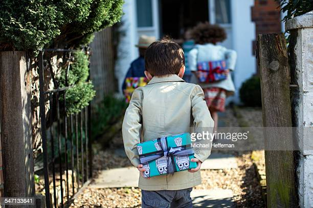 child holding present at birthday party - birthday stock pictures, royalty-free photos & images