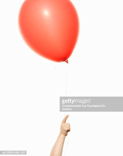 """child (2-3) holding red balloon, close-up of hand - """"compassionate eye"""" fotografías e imágenes de stock"""