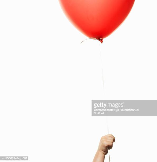 """child (2-3) holding red balloon, close-up of hand - """"compassionate eye"""" stock pictures, royalty-free photos & images"""