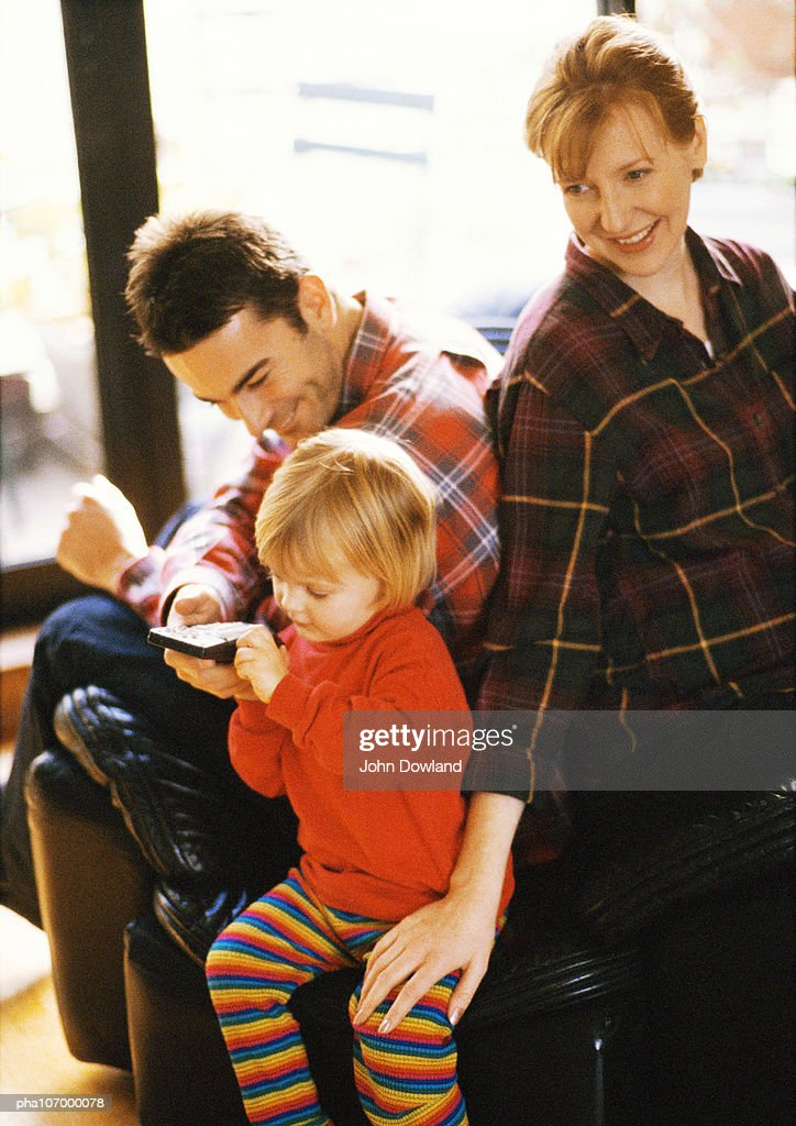Child holding remote control, couple sitting behind : Stock Photo