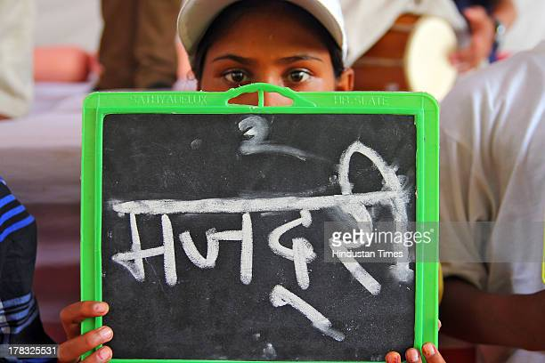 A child holding slate with Majdoori written on it during protest against child labour and right for the proper literacy organised by Bachpan Bachao...