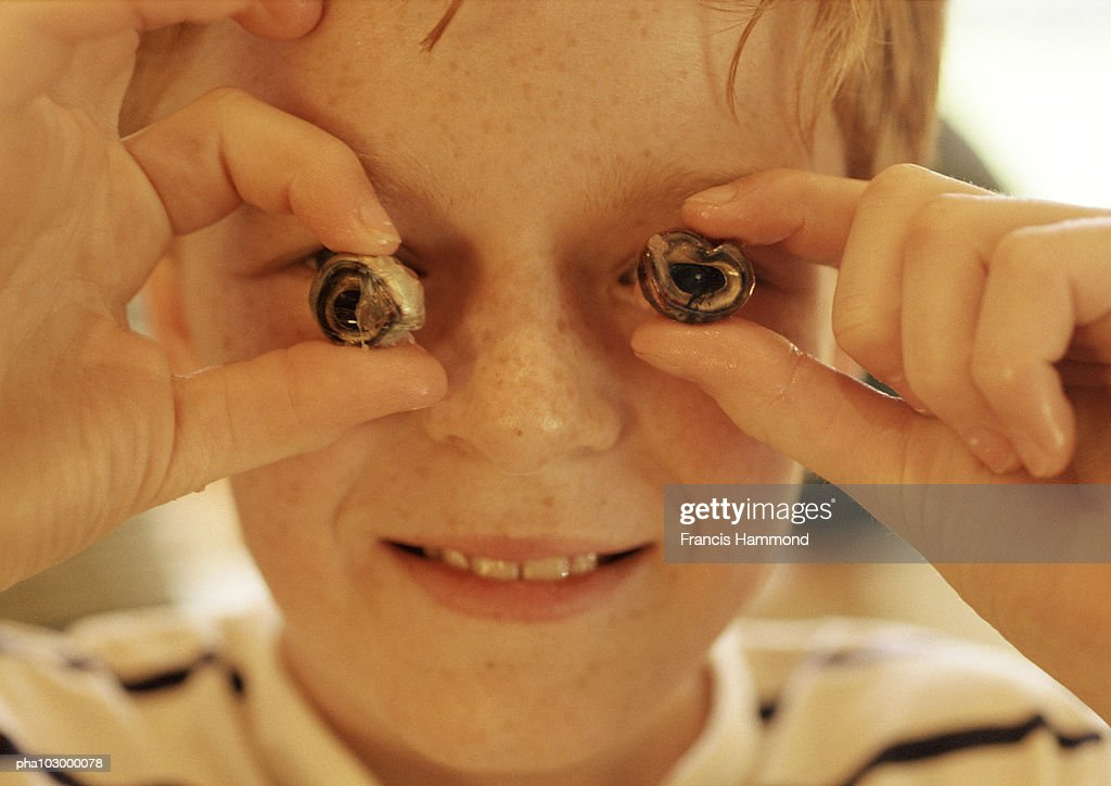 Child holding slices in front of eyes : Stockfoto
