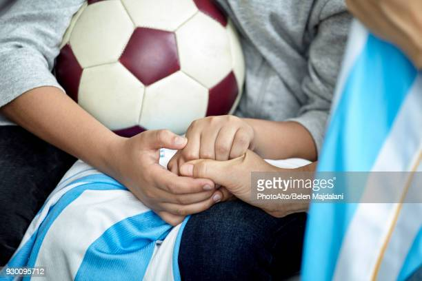 Child holding soccer ball, cropped