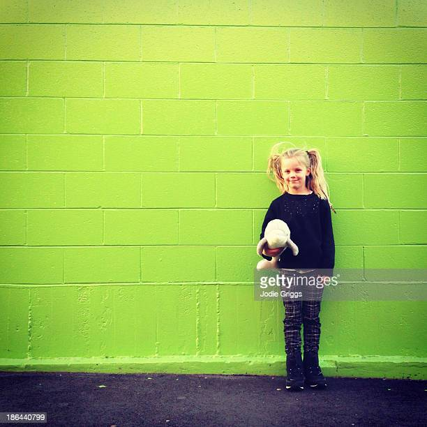 Child holding soft toy standing against green wall