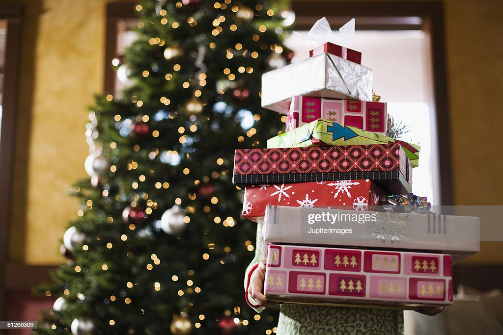 Child holding stack of Christmas gifts : Stock Photo