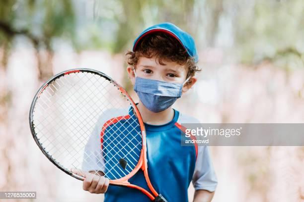 kind dat tennisracket met masker van de stofgezichtsbescherming houdt en camera bekijkt - racket sport stockfoto's en -beelden