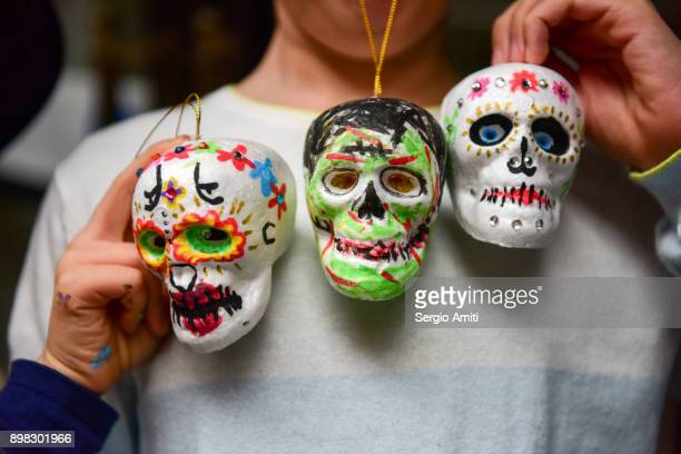 a child holding three hand painted polystyrene skulls at a halloween party - day of the dead festival stock photos and pictures