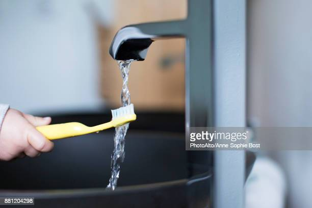 Child holding toothbrush under water faucet