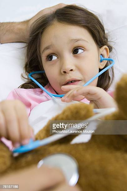 'Child holding toy stethoscope to teddy bear, talking to man'