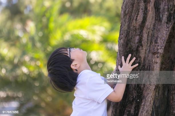 Child holding tree trunk.