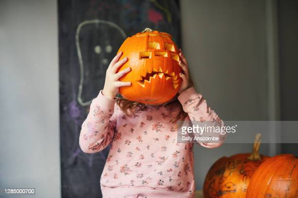 child holding up a pumpkin - sally anscombe stock pictures, royalty-free photos & images