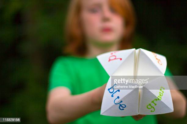 Child holding up handmade paper toy