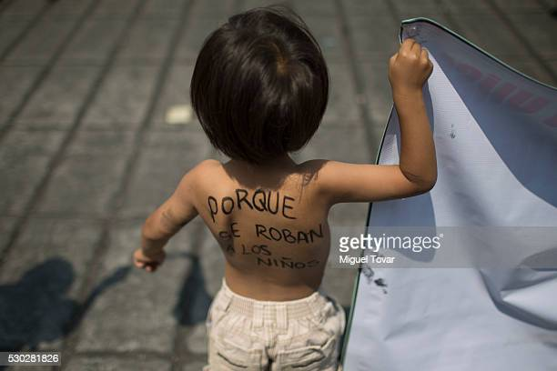 A child holds a banner during a march on Mother's Day on May 08 2016 in Mexico City Mexico Mothers and other relatives of persons gone missing in the...